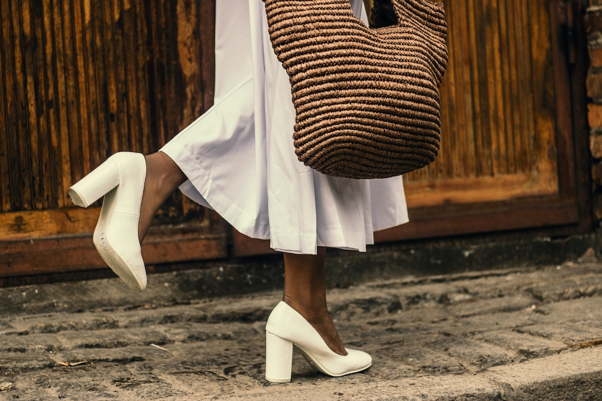 woman wearing white skirt and cream colored shoes