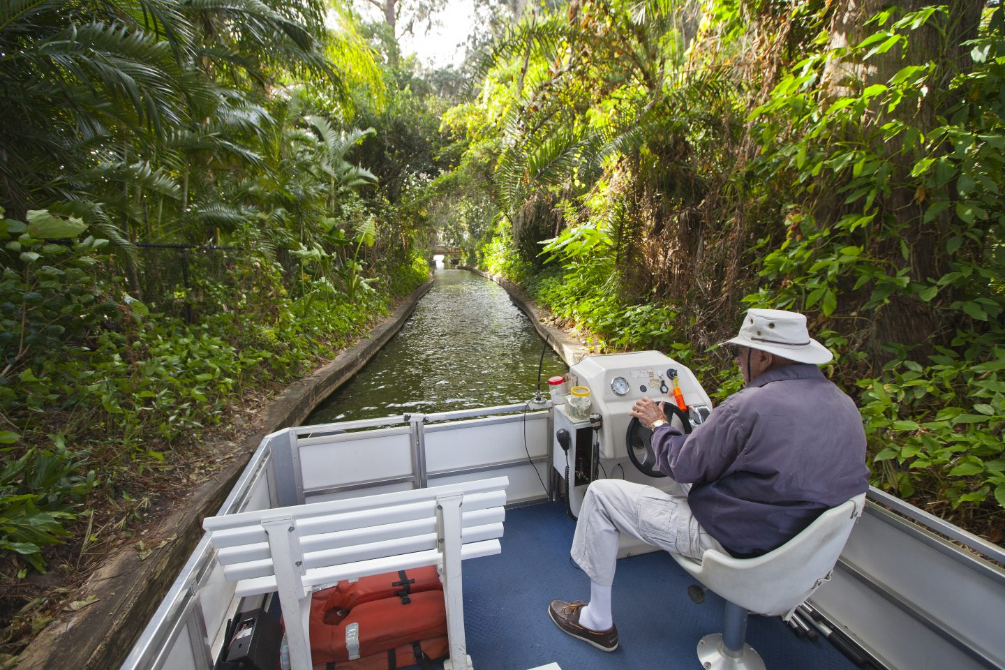 Things to do in Orlando for Adults the captain steers the boat through a canal on the Winter Park Scenic Boat Tour