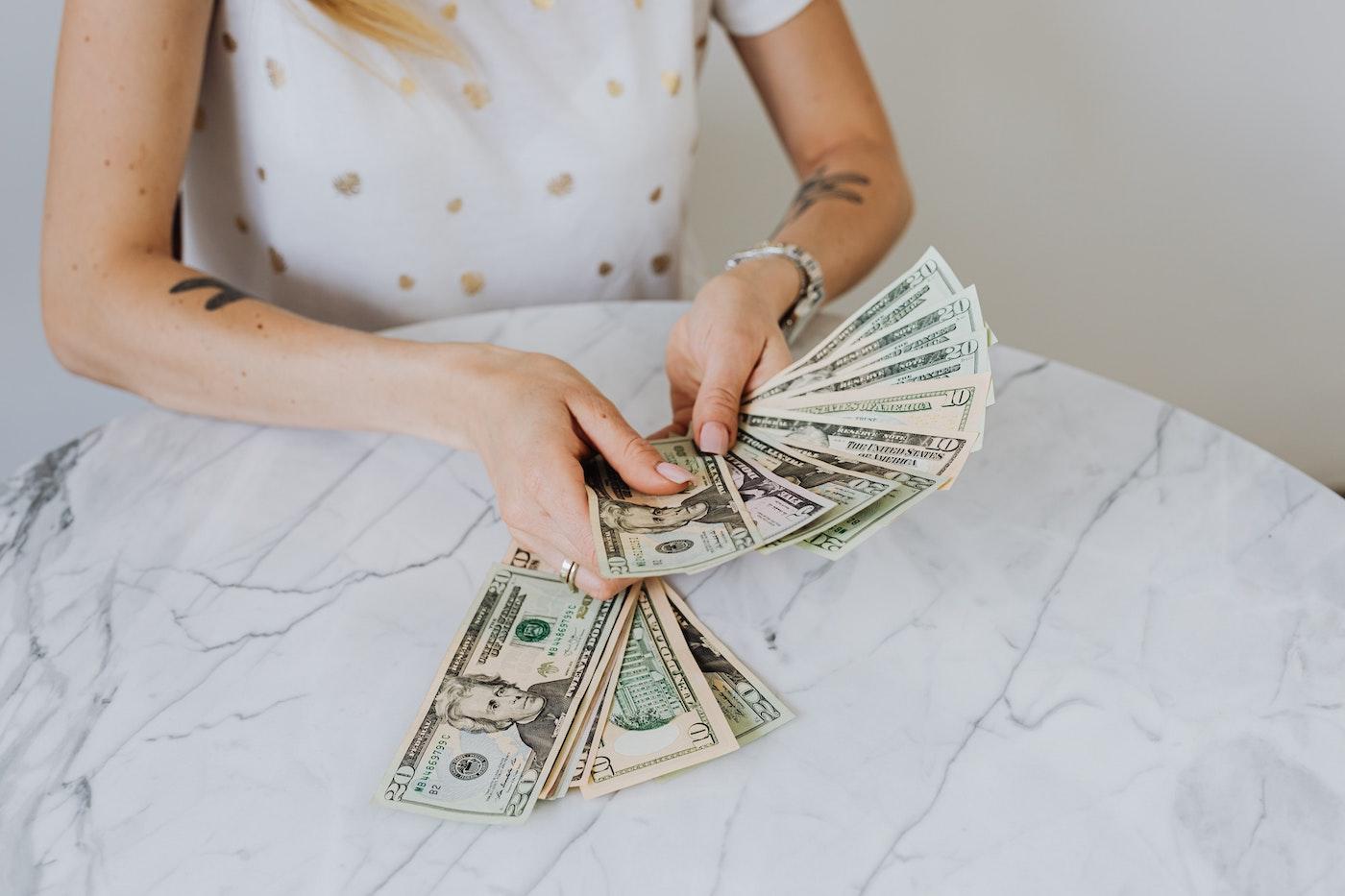 A women holding money. Overcoming money blocks.